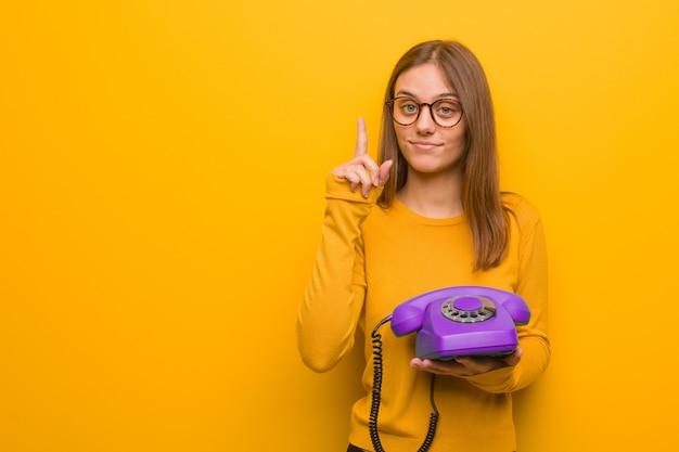 Junge hübsche kaukasische frau, die nummer eins zeigt. sie hält ein altes telefon in der hand.