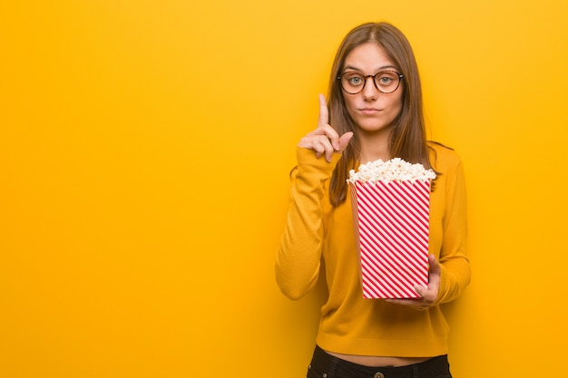 Junge hübsche kaukasische frau, die nummer eins zeigt. sie isst popcorn.