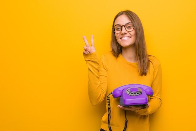 Junge hübsche kaukasische frau, die nummer zwei zeigt. sie hält ein altes telefon in der hand.