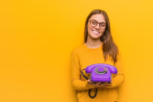 Junge hübsche kaukasische frau freundlich mit einem großen lächeln. sie hält ein altes telefon in der hand.