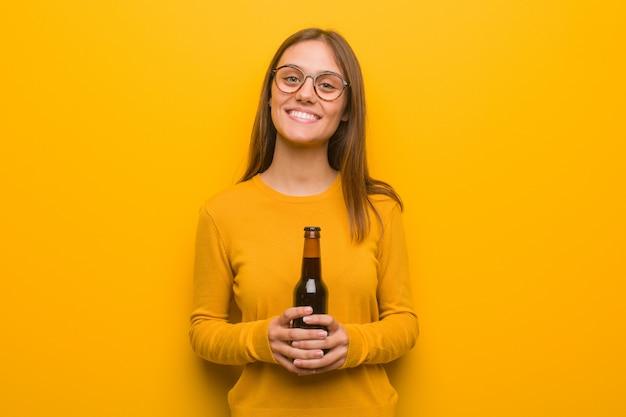 Junge hübsche kaukasische frau freundlich mit einem großen lächeln. sie hält ein bier.