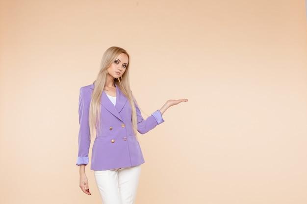 Junge hübsche kaukasische frau in lila und weißem anzug zeigt etwas auf ihrer hand isoliert auf hellem hintergrund