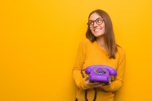 Junge hübsche kaukasische frau lächelnd zuversichtlich und arme kreuzen, nachschlagen. sie hält ein altes telefon in der hand.