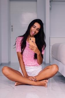 Junge hübsche kaukasische frau modeblogger, die stilvolle kleidung trägt und foto selfie macht