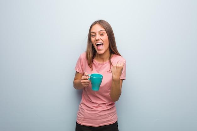 Junge hübsche kaukasische frau überrascht und entsetzt. sie hält eine tasse.