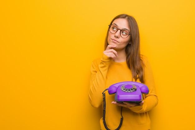 Junge hübsche kaukasische frau zweifelnd und verwirrt. sie hält ein altes telefon in der hand.