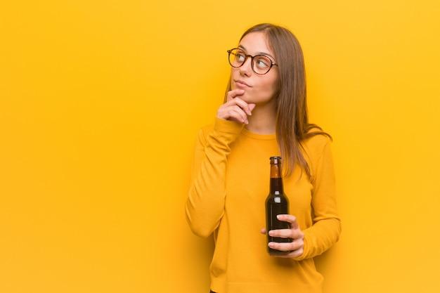Junge hübsche kaukasische frau zweifelnd und verwirrt. sie hält ein bier.
