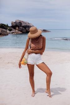 Junge hübsche kaukasische gebräunte passende frau in gestrickter kleidung am tropischen strand, der strohhut hält, der wiederverwendbaren ökologie-stringbeutel voller früchte apfelorangen-trauben hält