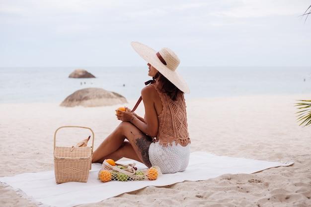 Junge hübsche kaukasische gebräunte passformfrau in gestrickter kleidung und mütze am strand