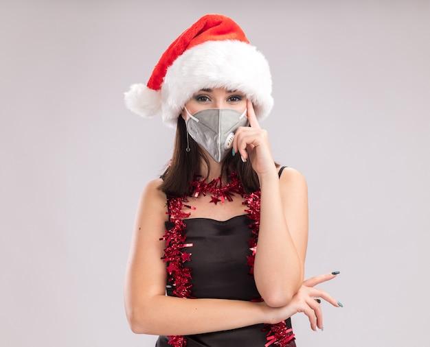 Junge hübsche kaukasische mädchen mit weihnachtsmütze und schutzmasken-lametta-girlande um den hals, die in die kamera schaut, die denkgeste einzeln auf weißem hintergrund mit kopienraum macht