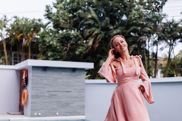 Junge hübsche kaukasische romantische frau allein im sommer süßes kleid im urlaub an luxusvilla