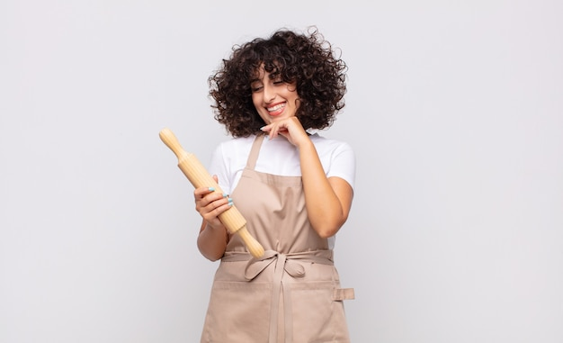 Junge hübsche köchin, die mit einem glücklichen, selbstbewussten ausdruck mit der hand am kinn lächelt, sich wundert und zur seite schaut