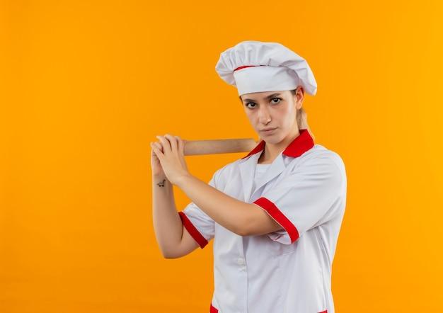 Junge hübsche köchin in der kochuniform, die nudelholz hält, das anfängt zu schlagen