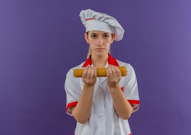 Junge hübsche köchin in der kochuniform, die spaghettinudeln sucht
