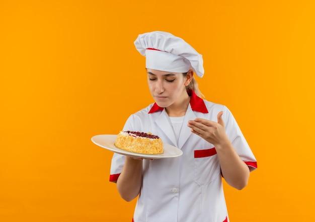 Junge hübsche köchin in der kochuniform, die teller des kuchens hält und schnüffelt, der hand auf luft hält