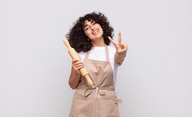 Junge hübsche köchin lächelt und sieht glücklich, sorglos und positiv aus, gestikuliert sieg oder frieden mit einer hand