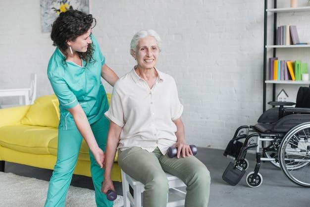 Junge hübsche krankenschwester, die alte frau in seiner therapie unterstützt