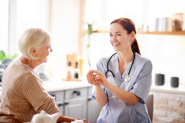 Junge hübsche krankenschwester, die vor der injektion lacht