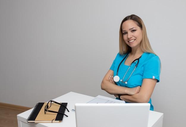 Junge hübsche krankenschwester in blauen kleidern mit einem stethoskop