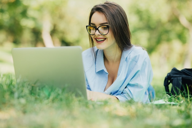 Junge hübsche lächelnde frau, die laptop im stadtpark am sonnigen tag verwendet