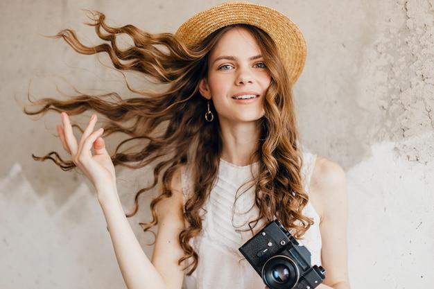 Junge hübsche lächelnde glückliche frau, die weiße bluse trägt, die gegen wand im strohhut sitzt
