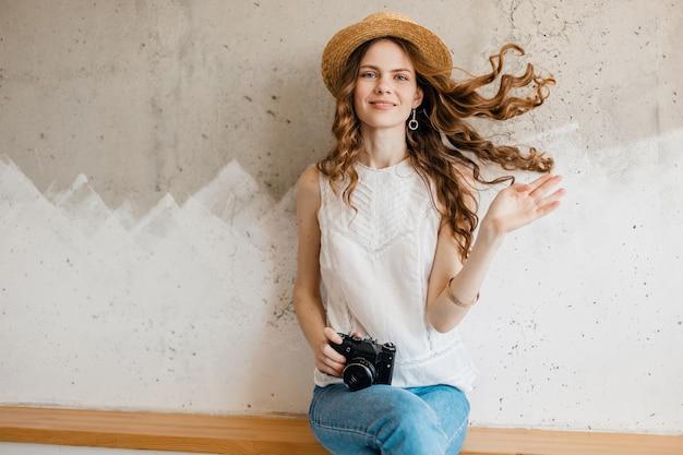 Junge hübsche lächelnde glückliche frau, die weißes hemd trägt, das gegen wand im strohhut sitzt