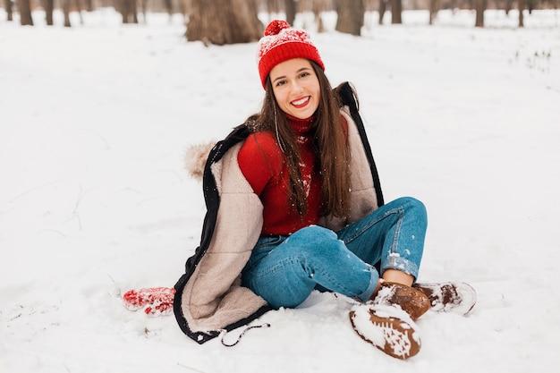 Junge hübsche lächelnde glückliche frau in den roten handschuhen und in der gestrickten mütze, die wintermantel trägt, der auf schnee im park, warme kleidung sitzt