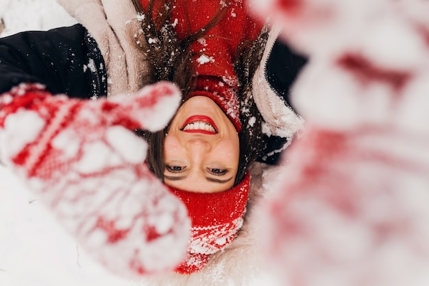Junge hübsche lächelnde glückliche frau in den roten handschuhen und in der gestrickten mütze, die wintermantel trägt, der im park im schnee, warme kleidung, ansicht von oben liegt
