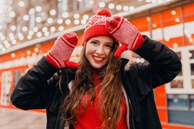 Junge hübsche lächelnde glückliche frau in den roten handschuhen und in der gestrickten mütze, die wintermantel trägt, der in der stadtweihnachtsstraße geht, warmer kleidungsstil-modetrend