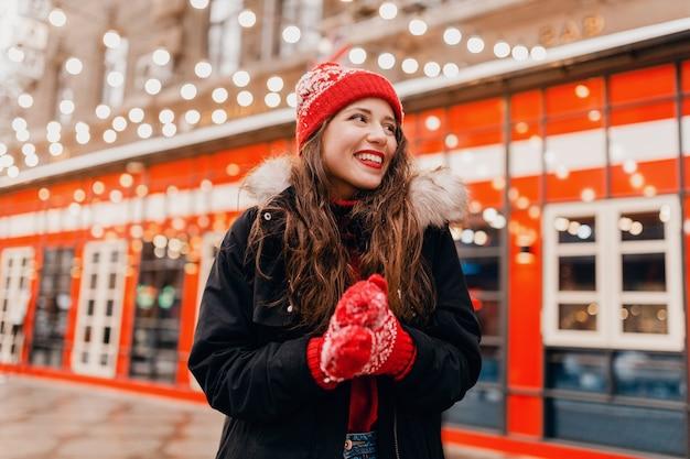 Junge hübsche lächelnde glückliche frau in den roten handschuhen und in der gestrickten mütze, die wintermantel trägt, der in stadtstraße, warme kleidung geht