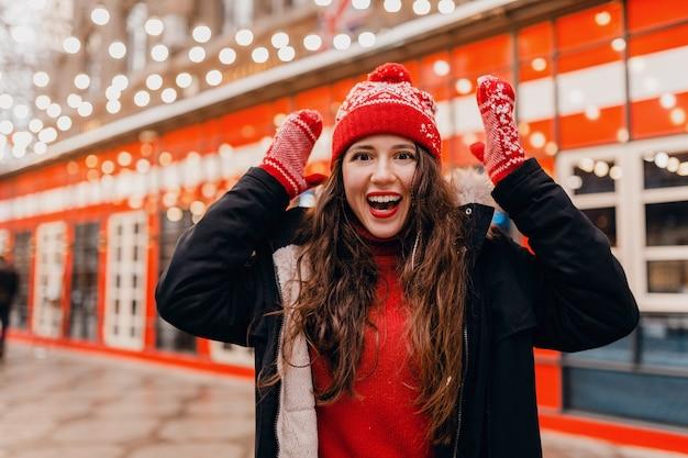 Junge hübsche lächelnde glückliche frau in den roten handschuhen und in der gestrickten mütze, die wintermantel trägt, der in stadtweihnachtsstraße, modetrend des warmen kleidungsstils, überraschten gesichtsausdruck geht