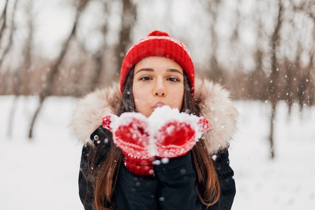 Junge hübsche lächelnde glückliche frau in den roten handschuhen und in der gestrickten mütze, die wintermantel tragen, im park gehen, schnee weht