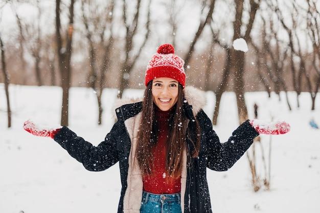 Junge hübsche lächelnde glückliche frau in den roten handschuhen und in der gestrickten mütze, die wintermantel tragen, im park spazieren gehen, mit schnee in der warmen kleidung spielen