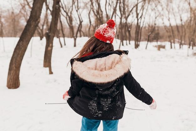 Junge hübsche lächelnde glückliche frau in den roten handschuhen und in der gestrickten mütze, die wintermantel tragen und im park im schnee, warme kleidung gehen