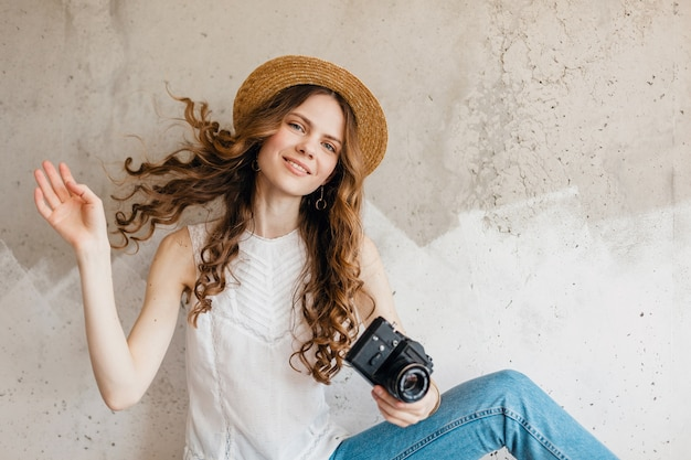 Junge hübsche lächelnde stilvolle frau, die blaue jeans und weißes hemd gegen wand im strohhut trägt