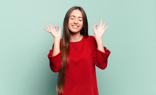 Junge hübsche lässige frau, die konzentriert und meditierend aussieht, sich zufrieden und entspannt fühlt, denkt oder eine wahl trifft