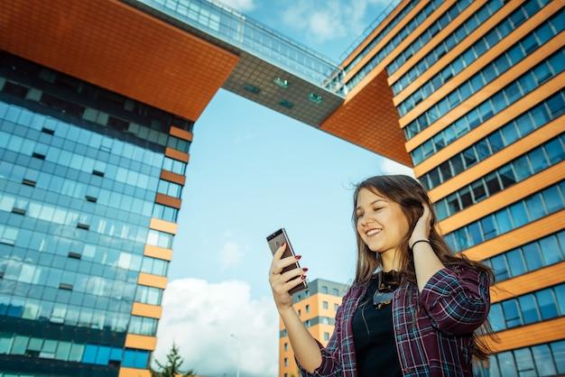 Junge hübsche langhaarige brünette in einem karierten hemd steht auf stadtstraße und kommuniziert mit smartphone. schönes mädchen dreht einen videoblog über das leben einer großstadt