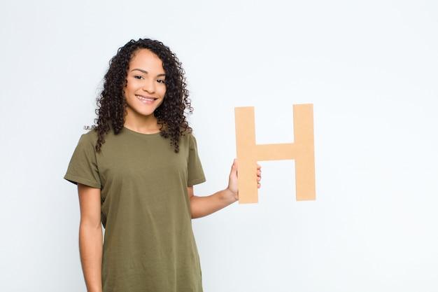 Junge hübsche lateinamerikanische frau aufgeregt, glücklich, freudig, den buchstaben h des alphabets haltend, um ein wort oder einen satz zu bilden