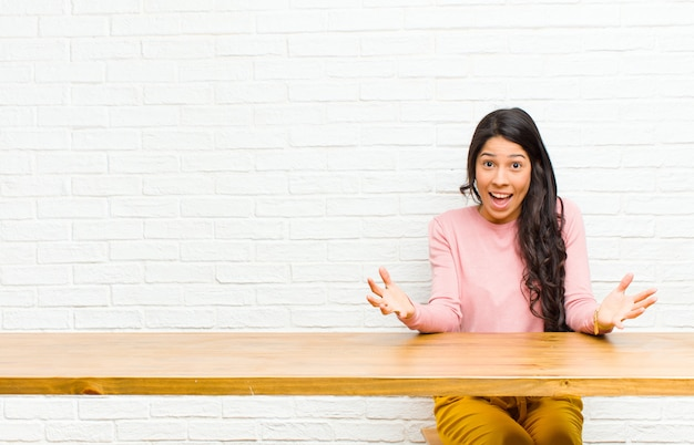 Junge hübsche lateinamerikanische frau, die sich glücklich, erstaunt, glücklich und überrascht fühlt, als würde sie ernsthaft omg sagen? unglaublich vor einem tisch zu sitzen