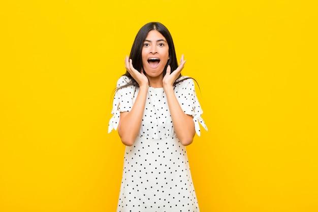 Junge hübsche lateinamerikanische frau, die sich schockiert und aufgeregt, lachend, erstaunt und glücklich wegen einer unerwarteten überraschung gegen flache wand fühlt