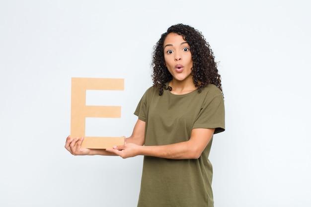 Junge hübsche lateinamerikanische frau überrascht, schockiert, erstaunt, den buchstaben e des alphabets haltend, um ein wort oder einen satz zu bilden.