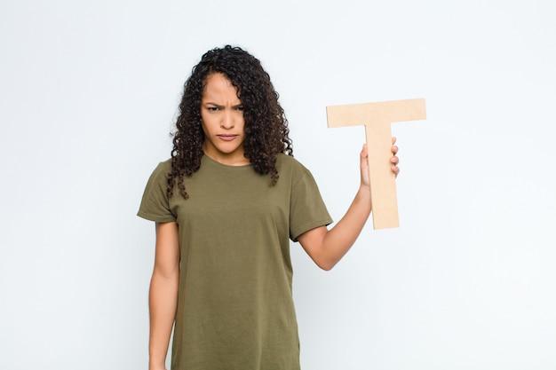Junge hübsche lateinamerikanische frau wütend, wut, uneinigkeit, den buchstaben t des alphabets haltend, um ein wort oder einen satz zu bilden.