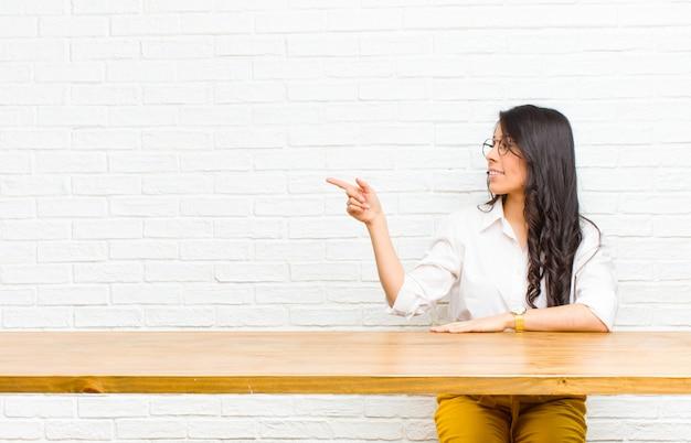 Junge hübsche lateinische frau, die auf gegenstand auf kopienraum, hintere ansicht sitzt vor einer tabelle steht und zeigt