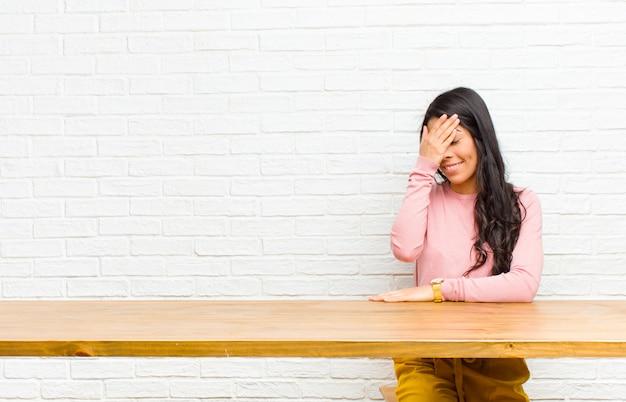 Junge hübsche lateinische frau, die betont, beschämt, mit kopfschmerzen, gesicht mit der hand bedeckend sitzt vor einer tabelle schaut