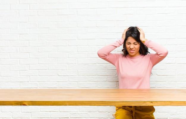 Junge hübsche lateinische frau, die betont und frustriert sich fühlt, hände zum kopf anhebt, müde, unglücklich und mit der migräne sich fühlt, die vor einer tabelle sitzt
