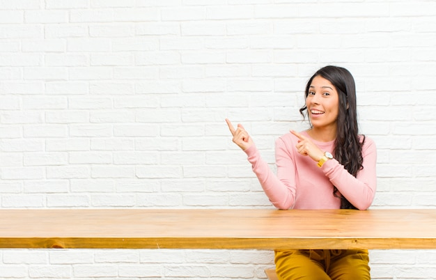 Junge hübsche lateinische frau, die glücklich lächelt und auf seite und aufwärts mit beiden händen zeigt gegenstand im kopienraum, der vor einer tabelle sitzt