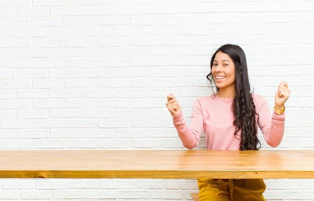 Junge hübsche lateinische frau, die glücklich, überrascht und stolz sich fühlt, erfolg mit einem großen lächeln schreit und feiert, das vor einer tabelle sitzt