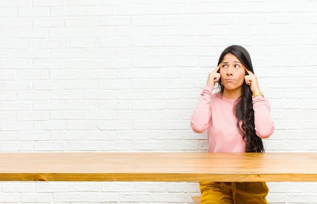 Junge hübsche lateinische frau, die konzentriert schaut und stark auf einer idee denkt und sich eine lösung für eine herausforderung oder ein problem vorstellt, die vor einer tabelle sitzen