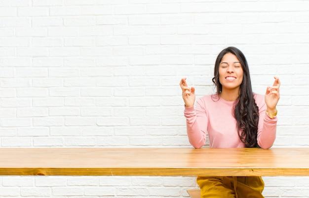 Junge hübsche lateinische frau, die nervös und hoffnungsvoll sich fühlt, finger kreuzt, für das gute glück sitzt vor einer tabelle betet und hofft