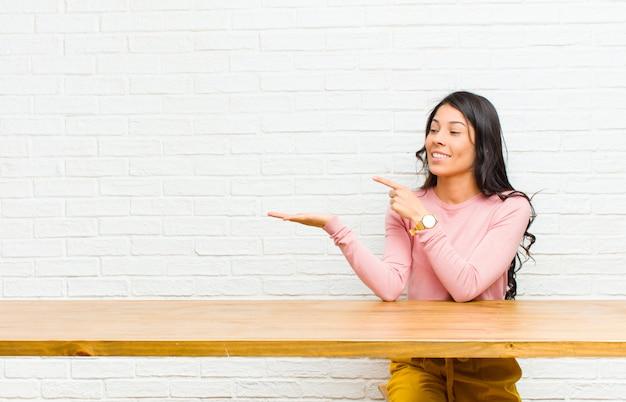 Junge hübsche lateinische frau, die nett lächelt und auf copyspace auf palme auf der seite zeigt, einen gegenstand zeigt oder annonciert, der vor einer tabelle sitzt